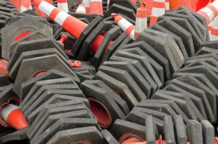 Stack of road repair construction orange pylon and barrels