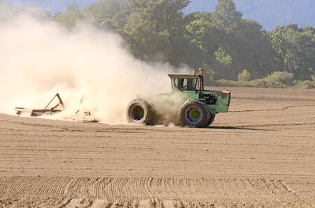 Ein großer Traktor tut abschließende Bodenvorbereitung mit einer Scheibenegge vor dem Einpflanzen Standard-Bild - 43922584