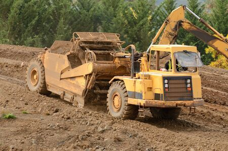 Large box scraper tractor works at moving soil and rock for a new commercial housing development. Stock Photo