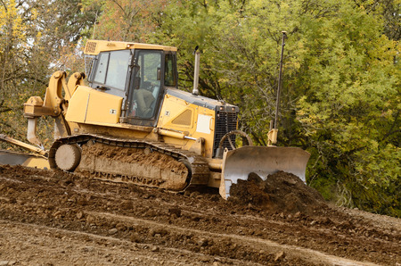 Bulldozer tractor works at moving soil and rock for a new commercial housing development. Stock Photo