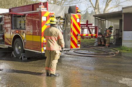 Roseburg OR, USA - 26. März 2014: Feuerwehrmänner, einen ersten Angriff auf eine Struktur Feuer von einem Mobilheim Standard-Bild - 44159231