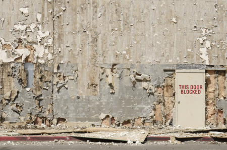 Blocked exit door on a building being remodeled but looks like a blast or war zone Stock Photo