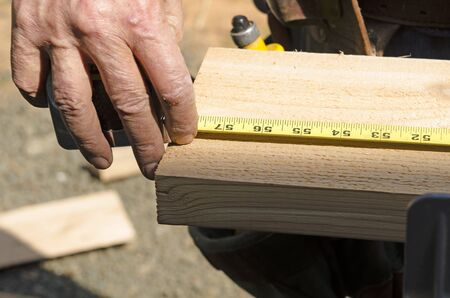 Wood siding contractor using a tape measure before cutting trim boards on the construction of a new home