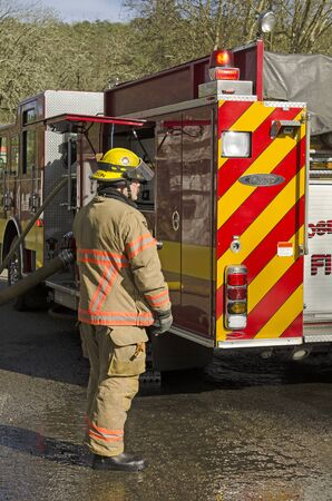 fire engine: Roseburg OR, USA - March 26, 2014: Fire engine and pump operator engineer on a structure fire of a mobile home