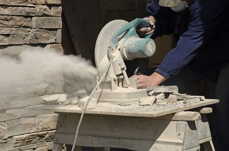 tile cladding: Masonry contractor using a dry circular tile or rock cutting saw to trim rock siding for a home installation Stock Photo
