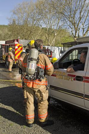 turnouts: Roseburg OR, USA - March 26, 2014: Fire incident commander fire chief discussing operations with firefighters on a structure fire of a mobile home Editorial