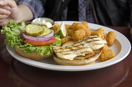 Grilled halibut fish hamburger sandwich with tater tots Standard-Bild