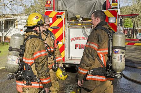 resplandor: Roseburg OR, EE.UU. - 26 de marzo de 2014: Los bomberos discutir las operaciones en un incendio en la estructura de una casa móvil