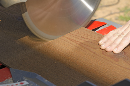 miter: Wood siding contractor using a electric compound miter saw to cut window and door trim boards on the construction of a new home