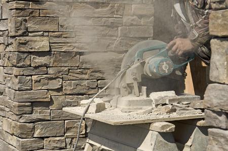 마른 원형 타일 또는 바위 절단을 사용하여 벽돌 계약자는 홈 설치 바위 사이딩을 잘라 보았다 스톡 콘텐츠