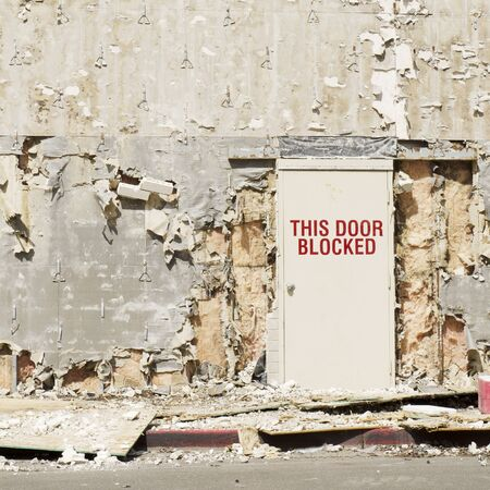 Blocked exit door on a building being remodeled but looks like a blast or war zone Standard-Bild