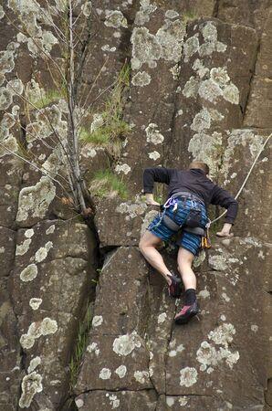 Young man rock climbing at Skinner Butte Climbing Columns. Popular public rock climbing area  in Eugene Oregon.