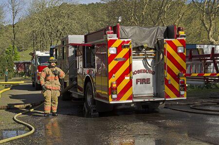 Roseburg OR, USA - 26. März 2014: Feuer-Motor und Pumpenbetreiber Ingenieur auf einer Struktur Feuer von einem Mobilheim Standard-Bild - 44159229