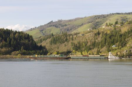 A grain barge pushed by a tugboat travels down the Columbia River in Oregon