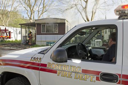 batallón: Roseburg OR, EE.UU. - 26 de marzo 2014: jefe de bomberos comandante de Bomberos incidente operaciones que dirigen en un fuego de la estructura de una casa móvil Editorial