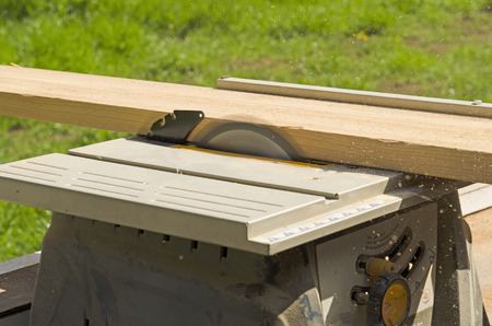 Wood siding contractor using a table saw to cut window and door trim boards on the construction of a new home