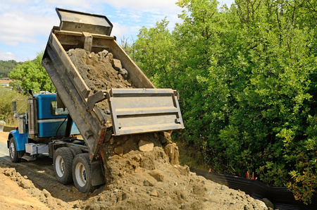 로즈버그 오레곤, 미국 - 8 월 (11) 2012 - 10 야드 덤프 트럭은 새로운 도로 건설 프로젝트에 바위와 흙의로드 덤프