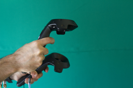 Man hands holding VR controls on a green background