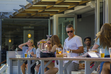 People enjoying a beer at the outside bar terrace Editorial