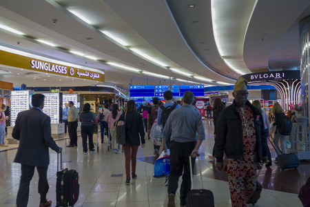 People with baggage walking in Airport duty free area
