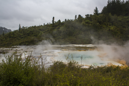 Steam rising from colorful terrace on geothermal landscape