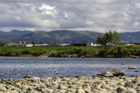 Peaceful landscape with river flowing and green mountains on the background