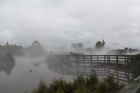 Misty River and wood bridge disappearing into the fog. Beautiful Geothermal landscape