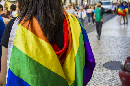Girl with a rainbow flag watching the pride parade Imagens