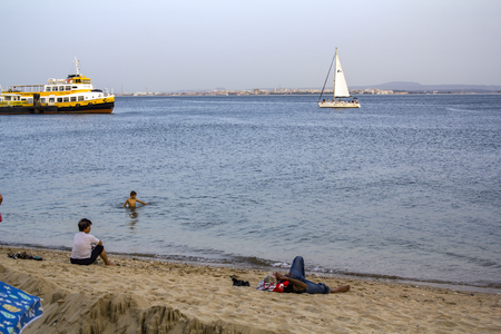 People are cooling at tagus river on one of the hottest summer days in Portugal Editorial