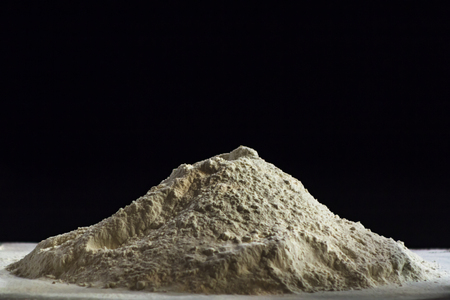 Pile of flour on black background with copy space