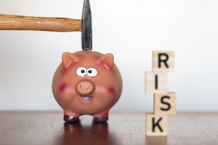 Hand holding a hammer above a Piggy bank and Risk word written on wooden cubes