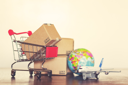 Shopping cart with cartons, airplane and earth globe. Vintage effect