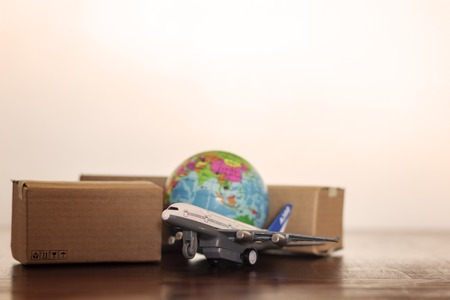Cartons with airplane and earth globe. International delivery and global logistics concept