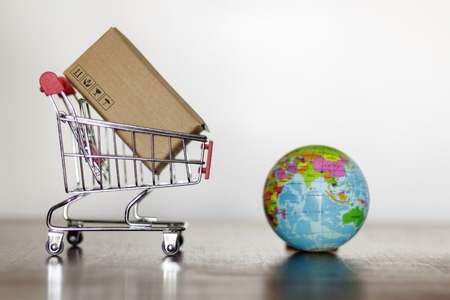 Trolley with carton and earth globe. Worldwide shopping and delivery business concept