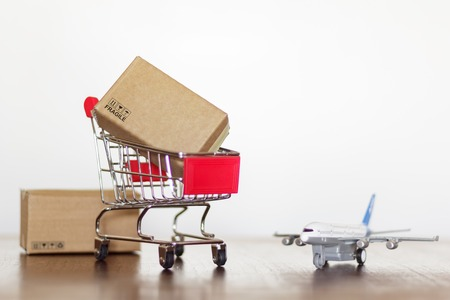 Shopping cart with boxes and airplane. Worldwide Shopping and shipping concept