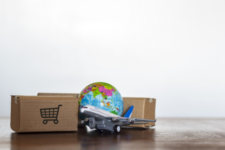 Cartons with airplane and earth globe. Global logistics, shipping and worldwide delivery business concept Standard-Bild