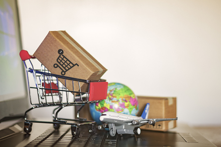Trolley with cartons, globe and airplane on computer. Online Shopping and International shipping concept