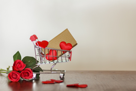 Trolley with carton and red hearts. Shopping for valentines day concept