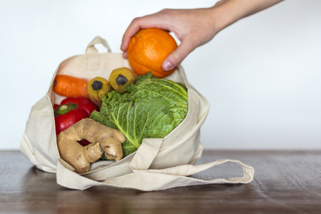 Woman taking a orange from eco bag with groceries