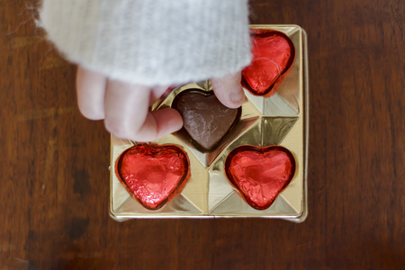 Woman's hand taking a chocolate heart from candie box