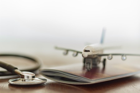Stethoscope , passport document and airplane: Medical Travel concept