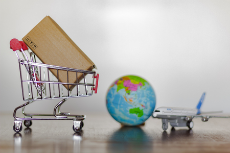 Trolley with carton, airplane and planet earth. International delivery and global logistics concept