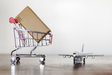 Trolley with carton and airplane. Shopping and International shipping concept Standard-Bild