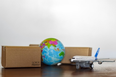 Cartons, airplane and earth globe. International delivery and global logistics concept Standard-Bild