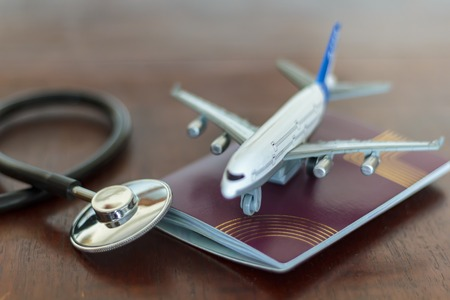 Medical Stethoscope , passport and an airplane. Global Healthcare and travel insurance concept Фото со стока