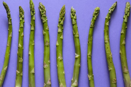 Top view of green asparagus against purple background Stock Photo