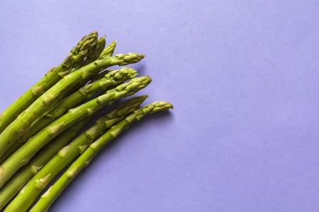 Top view of fresh green asparagus against purple background with copy space
