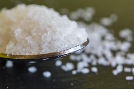 Close up of Spoon with coarse grained sea salt on black background Reklamní fotografie