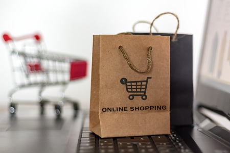 Shopping bags and trolley on laptop. Online shopping, e-commerce concept Banco de Imagens