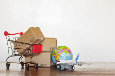 Shopping cart with cartons, airplane and earth globe. Global logistics, shipping and worldwide delivery business concept